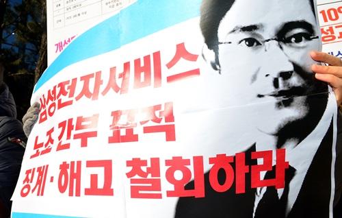 전국금속노동조합 삼성전자서비스지회원이 이재용 삼성전자 부회장의 그림이 그려진 피켓을 들고 있다. 사진은 기사 내용과 무관함. 제공= 뉴시스