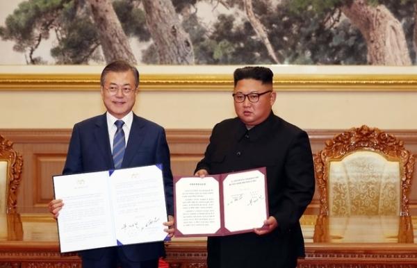 문재인 대통령과 김정은 국무위원장이 19일 백화원 영빈관에서 정상회담을 마친 뒤 평양공동선언서에 서명한 뒤 펼쳐 보이고 있다.