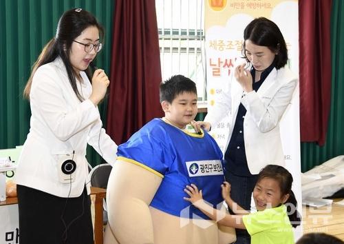 어린이가 비만조끼를 입고 가상비만체험을 하고 있다.Ⓒ광진구