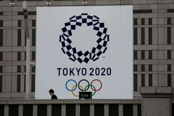 도쿄 소재 한 건물에 설치된 2020년 도쿄올림픽 현수막 앞을 시민이 지나가고 있다. ⓒ뉴시스